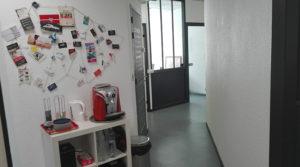 Hall d'entrée des Bureaux de Bordo Buro avec machine à café et vue sur les bureaux